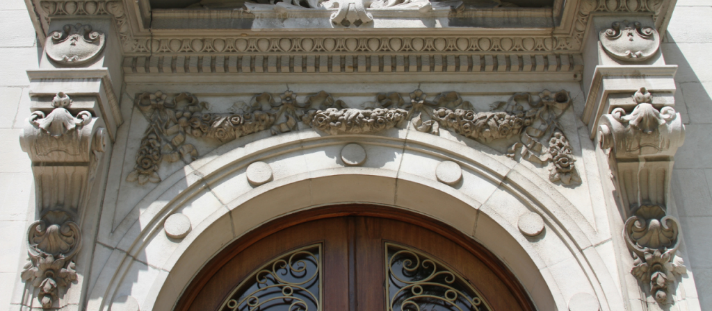 The front entrance features a prominent round arch of the doorway and the grilled openings let into the frieze of the entablature.