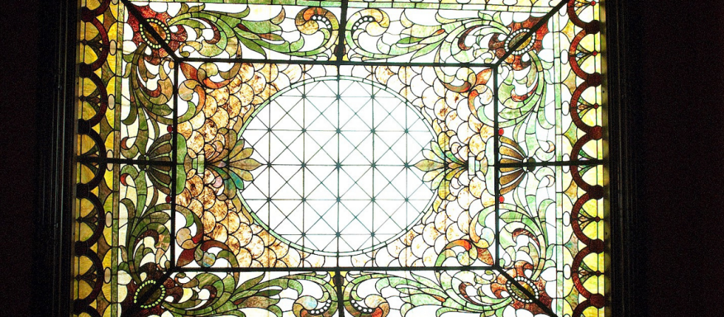 Original leaded stained glass skylight that illuminates the grand central staircase.